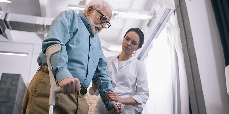 medica oferecendo um atendimento preferencial para um senhor de muletas